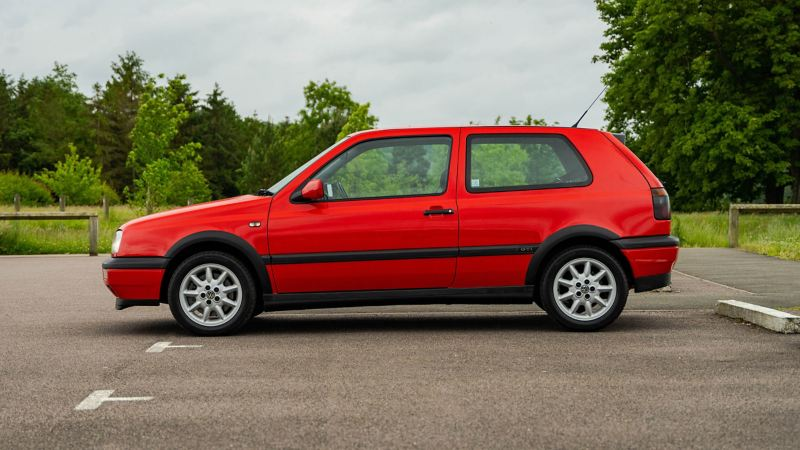 A side profile shot of a red Mk3 VW Golf GTI