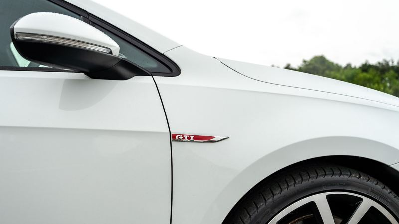 A side profile shot of a white Mk 7 VW Golf showing GTI logo and wing mirror