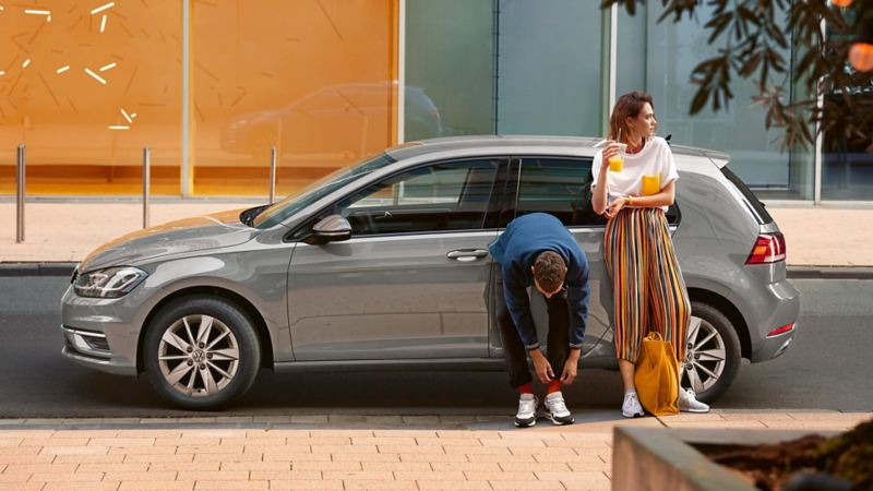 Man and woman leaning against a VW Golf