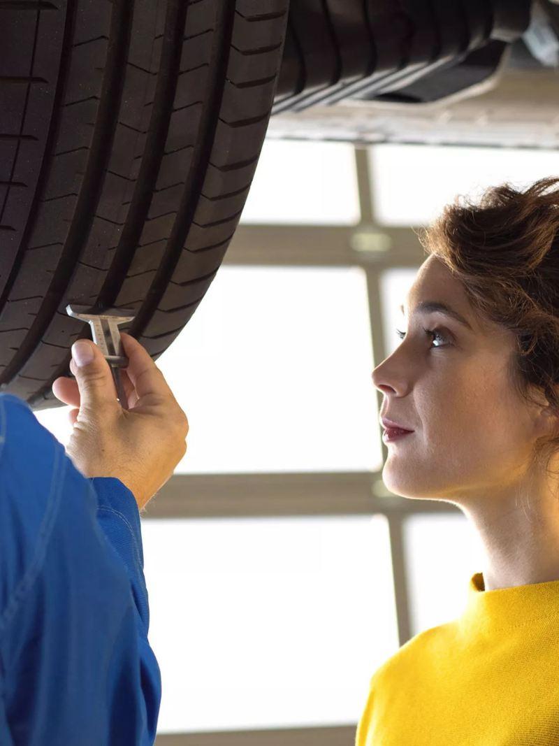 Une femme inspectant sa Volkswagen avec un spécialiste, lien vers la page rendez-vous