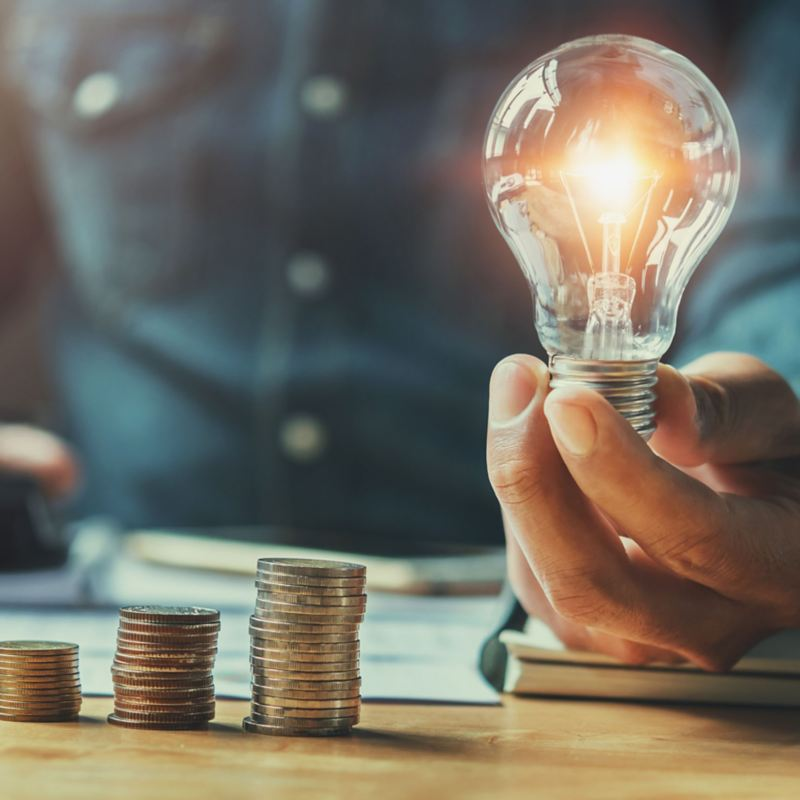 Mann mit leuchtender Glühbirne und Stapel von Münzen: Durch die Förderung sind E-Autos als Gesamtpaket finanziell attraktiv.