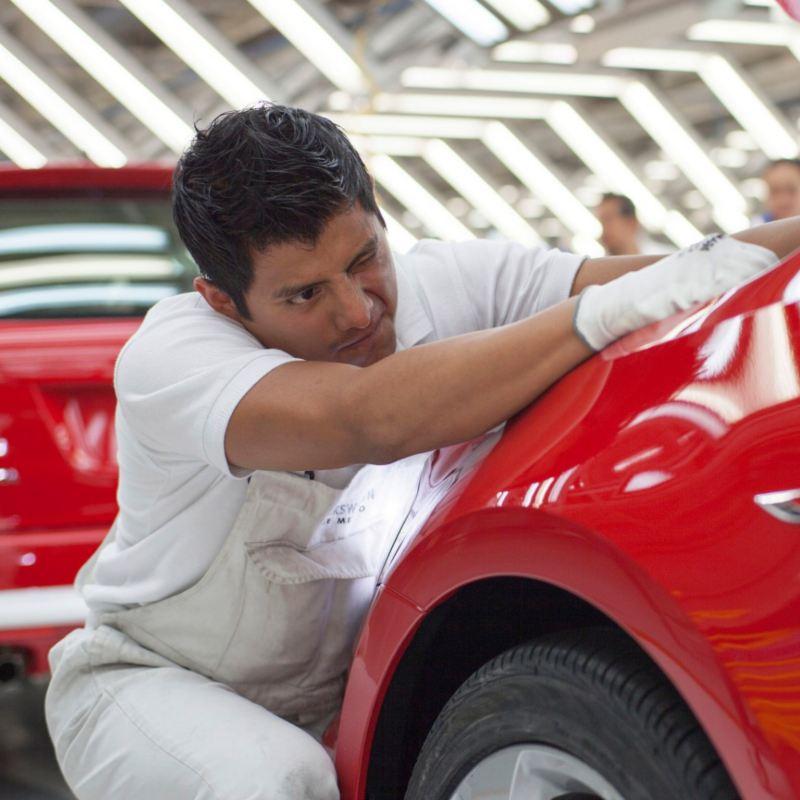 Trabajador puliendo pintura de automóvil en planta Volkswagen de México