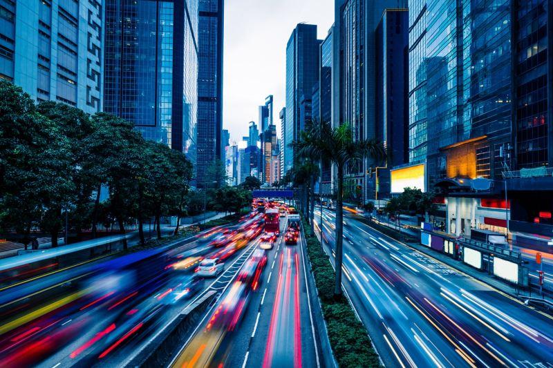 Mehrspurige Straße mit Fahrzeugen in einer Großstadt.