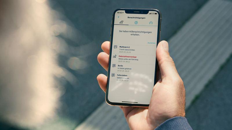 Un homme regarde son smartphone sur lequel l'application We Connect avec le service d'alarme antivol en ligne est ouverte.