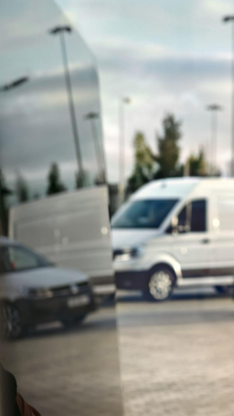 Eine Frau am Telefon, im Hintergrund ihre Flotte von VW Nutzfahrzeuge.