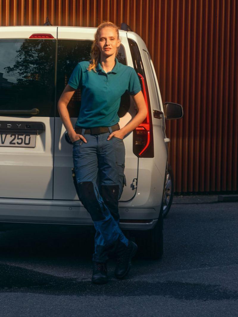Een vrouw leunt tegen de achterste klapdeuren van de nieuwe Volkswagen Caddy Cargo.