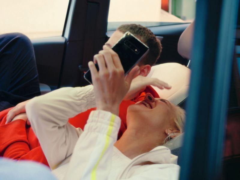 Una giovane coppia che ride sui sedili reclinati di una Volkswagen ID.3
