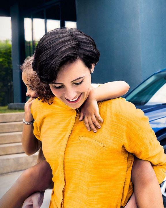 Frau mit Kind auf dem Rücken vor einem VW Tiguan