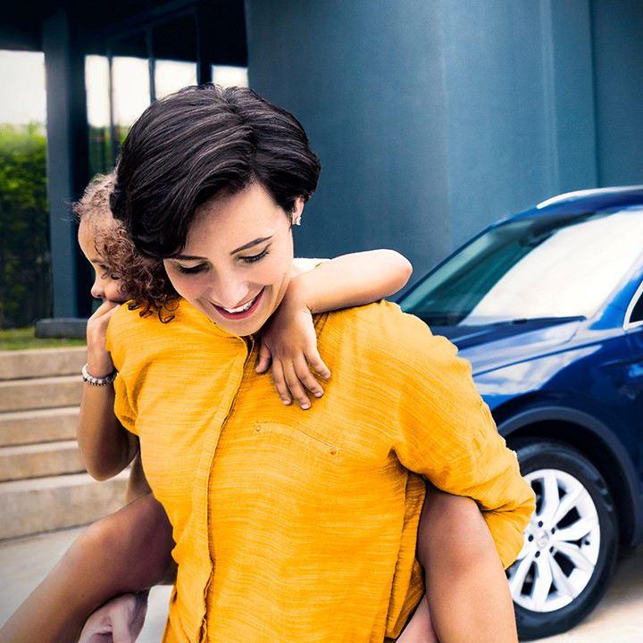 Keltapaitainen nainen jolla on pieni tyttö reppuselässä kävelee pois Volkswagen Tiguanin luota