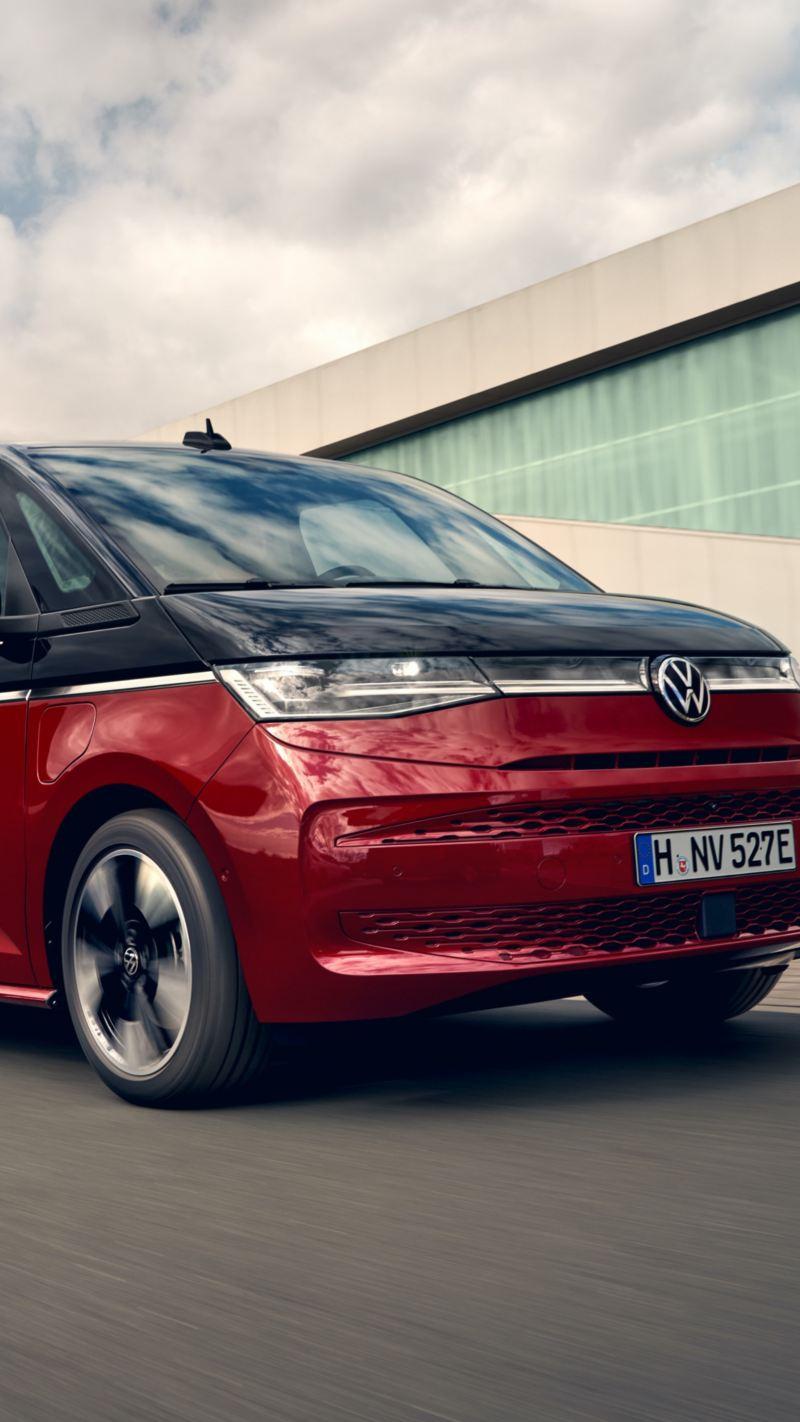 Bildet viser den nye Volkswagen T7 Multivan ehybrid ladbar hybrid i sort og rød som kjører på veien