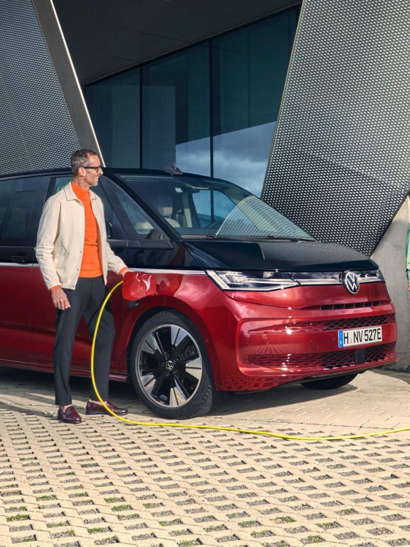 Ein Mann steckt das Kabel zum Laden des VW Multivan in das Fahrzeug.