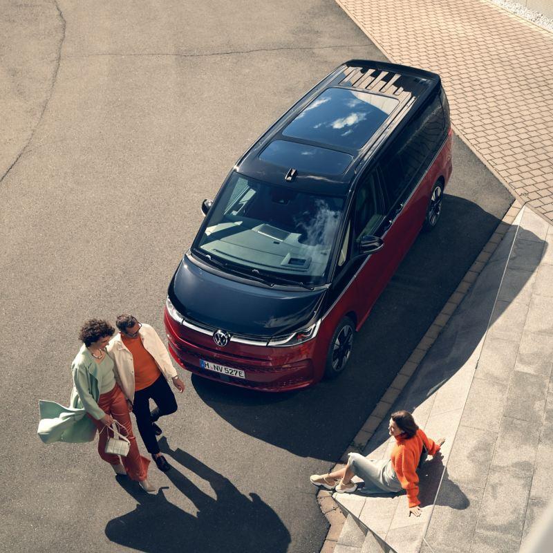 Eine Gruppe Menschen vor einem VW Multivan Style schräg von oben.