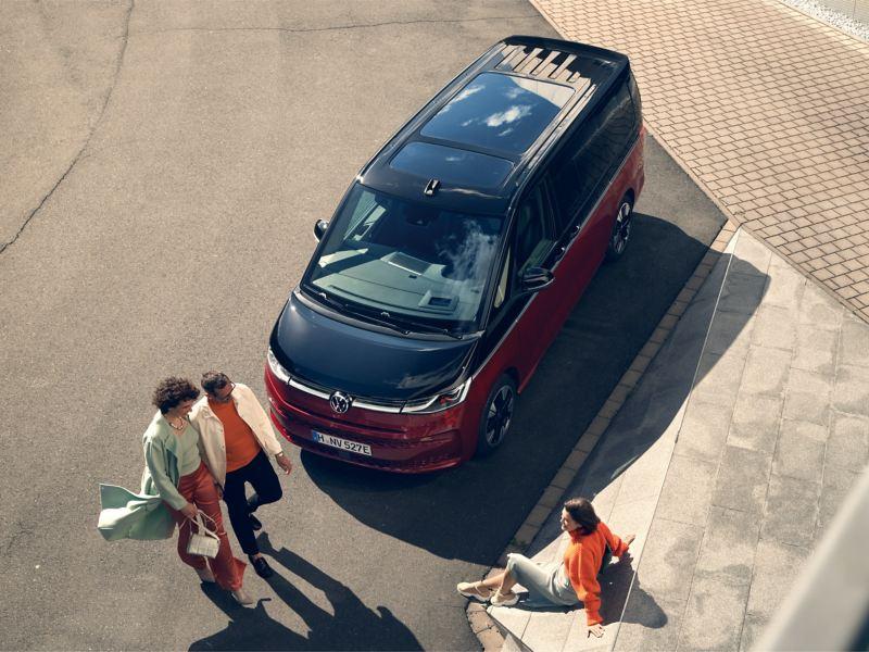 Un gruppo di persone davanti a VW Multivan Style, vista obliqua dall'alto.