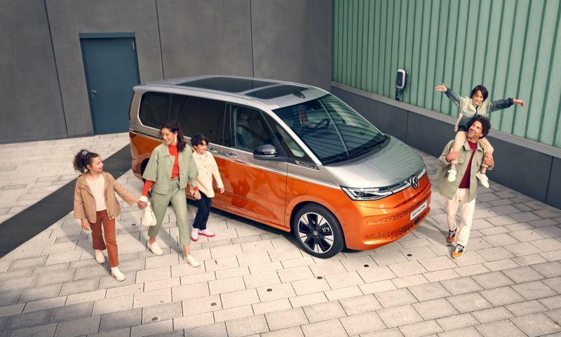 Zadowolona rodzina podchodzi do parkującego VW Multivan Energetic
