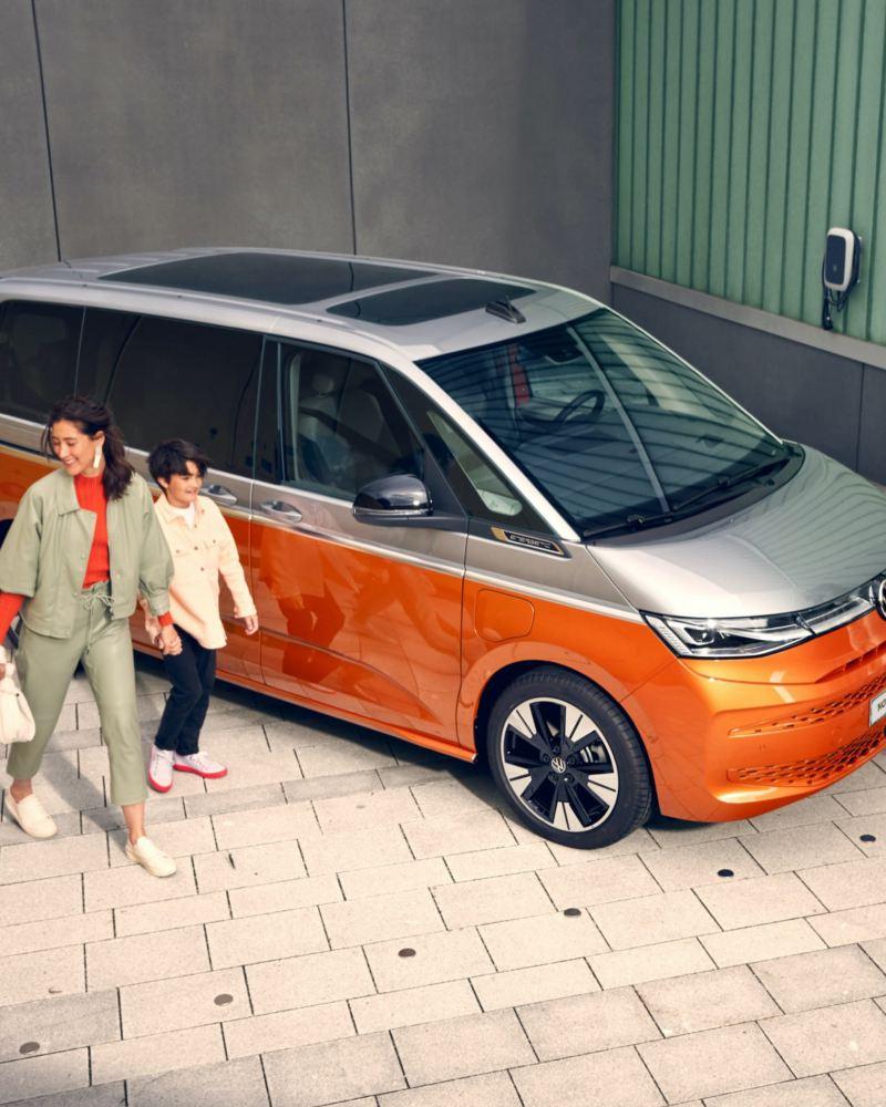 Zadowolona rodzina podchodzi do parkującego VW Multivan Energetic.