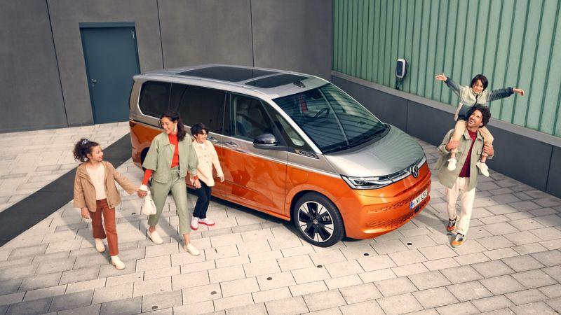 Bildet viser en familie som står og løper rundt den nye Volkswagen T7 Multivan ehybrid ladbar hybrid i orange og grå