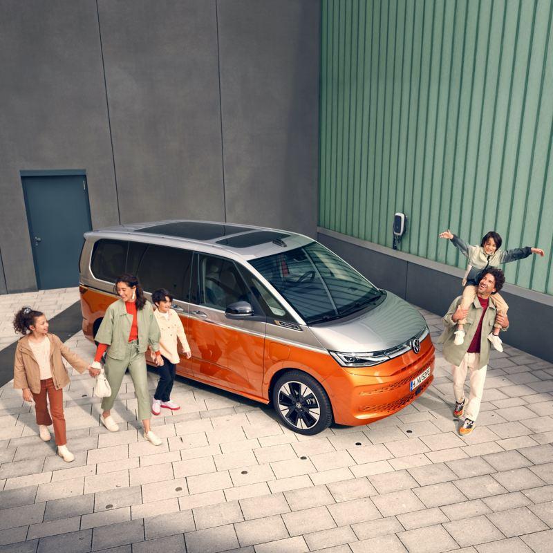 Una famiglia cammina allegramente accanto a VW Multivan Energetic fermo.