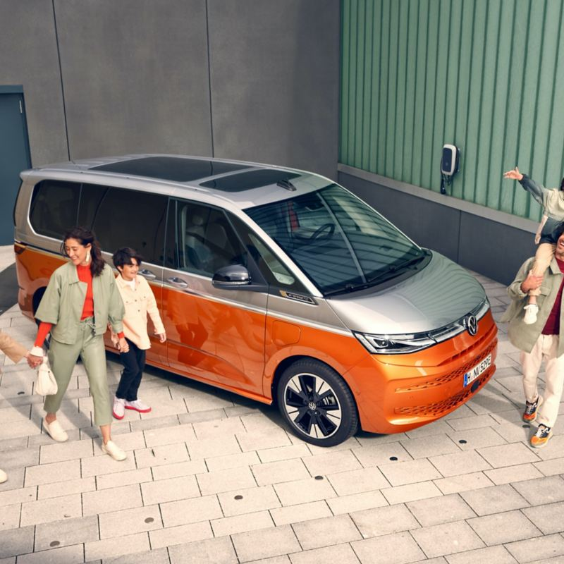 Une famille marche, tout sourire, à côté du VW Multivan Energetic en stationnement.