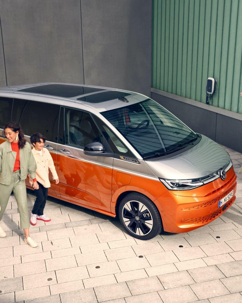 Eine Familie läuft vergnügt neben den stehenden VW Multivan Energetic her.