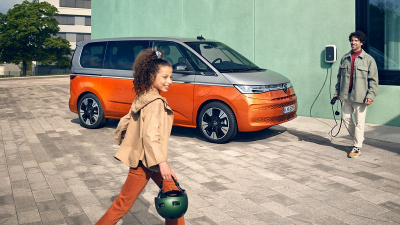 A man with a charging cable in his hand and a girl with a helmet in front of the VW Multivan Energetic.
