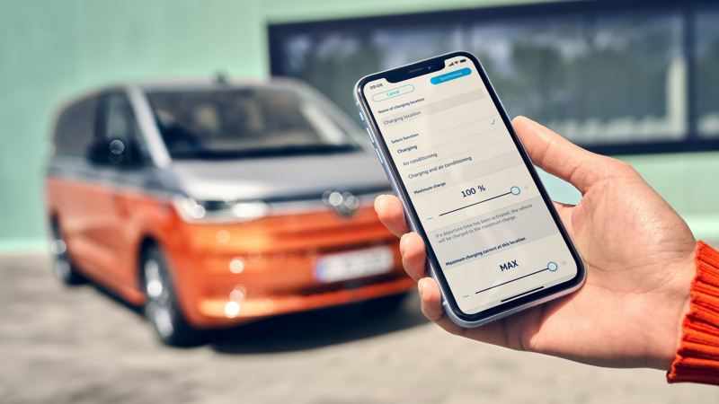 A hand holds a smartphone. In the background, the VW Multivan Energetic can be seen in a blur.