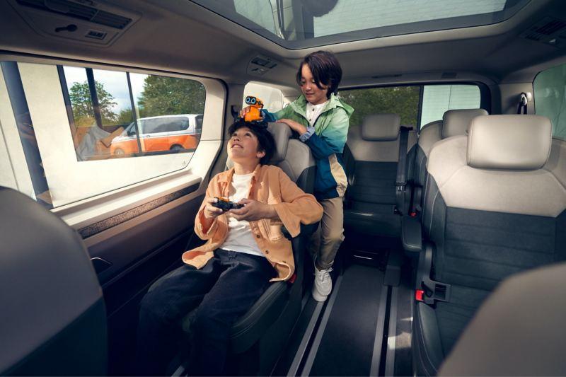 Deux garçons à l'intérieur du VW Multivan jouant avec des jouets.