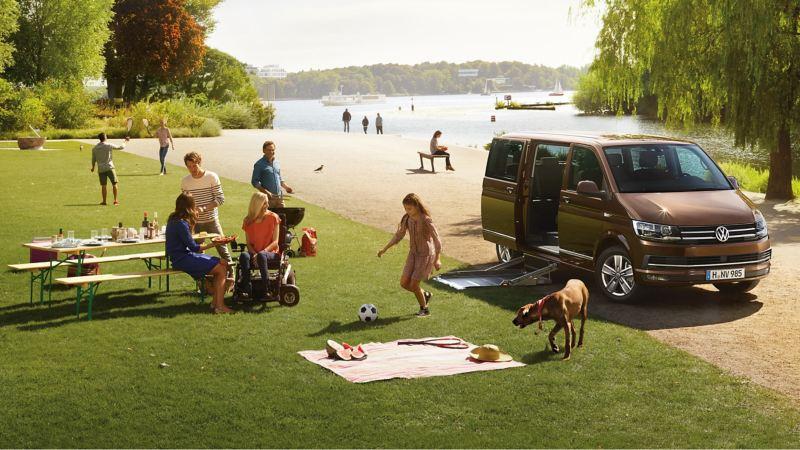 Eine Familie spielt im Park neben einen Multivan.