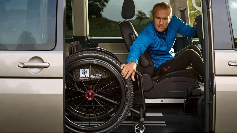 Ein Rollstuhlfahrer sitzt auf dem Fahrersitz und verstaut seinen Rollstuhl.