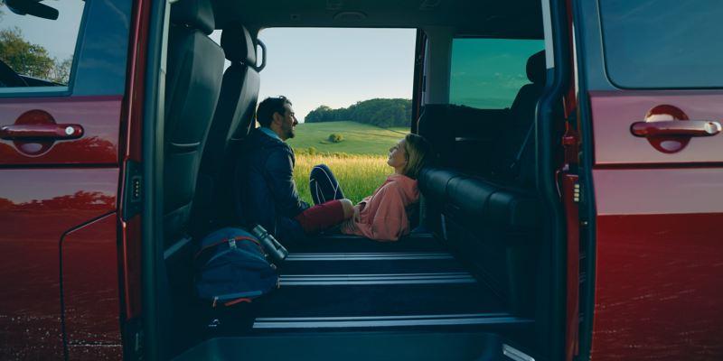 Ein mann und eine Frau sitzen in der Tür vom Multivan 6.1.