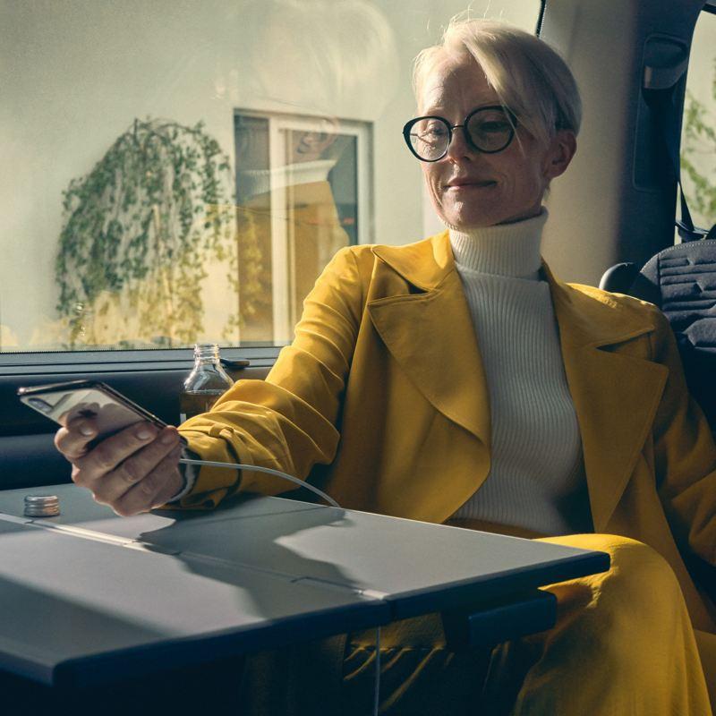 Une femme est assise dans une Volkswagen et active l'application We Connect sur son smartphone.