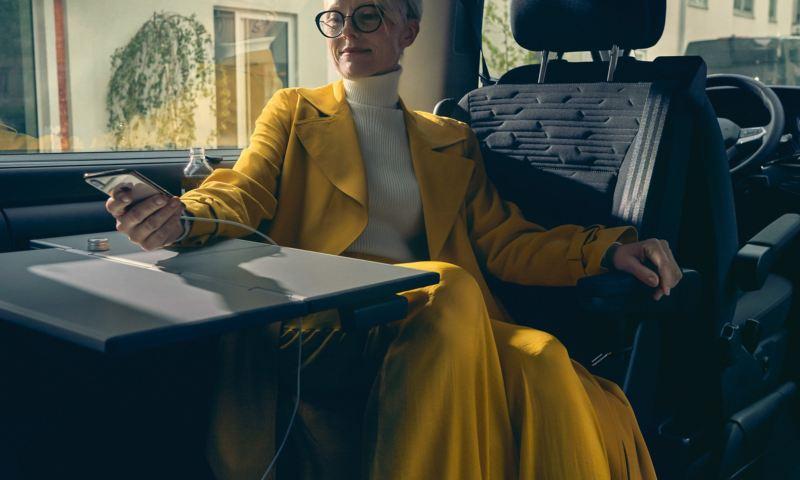 Kobieta w żółtym płaszczu siedzi w Volkswagenie Multivan 6.1 przy stole i ładuje swój telefon.