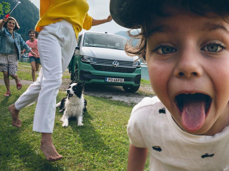 Dziecko wyciąga język do aparatu. W tle zielono-biały Volkswagen Multivan oraz dwoje dzieci, kobieta i pies leżący na trawie.