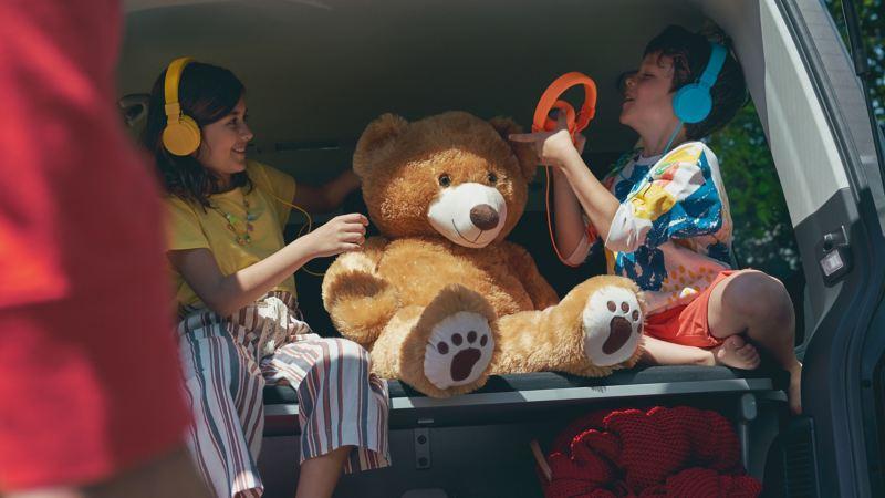 Deux enfants assis dans le coffre aménagé d'une Volkswagen avec des écouteurs.