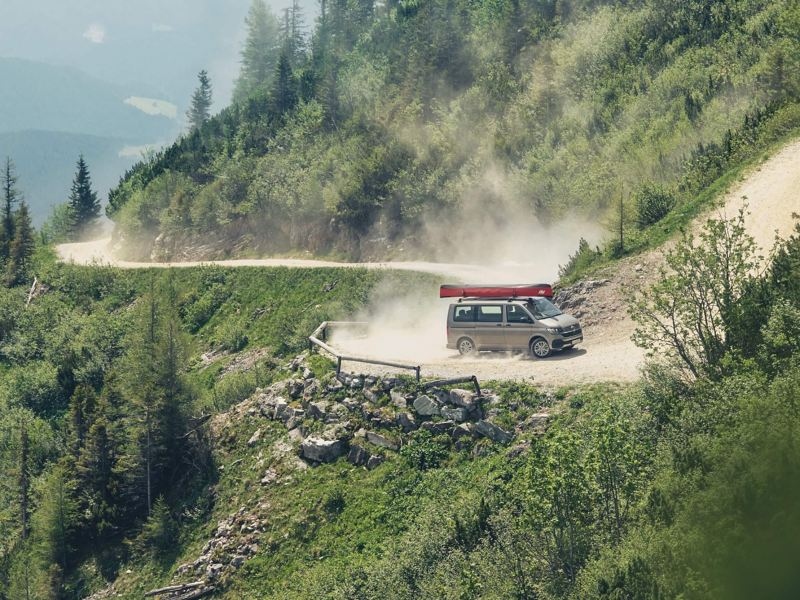 IQ.DRIVE情境圖 - T6.1 Multivan行駛在山腰上的蜿蜒石礫小路,塵土飛楊顯示車款操控及性能安全無虞