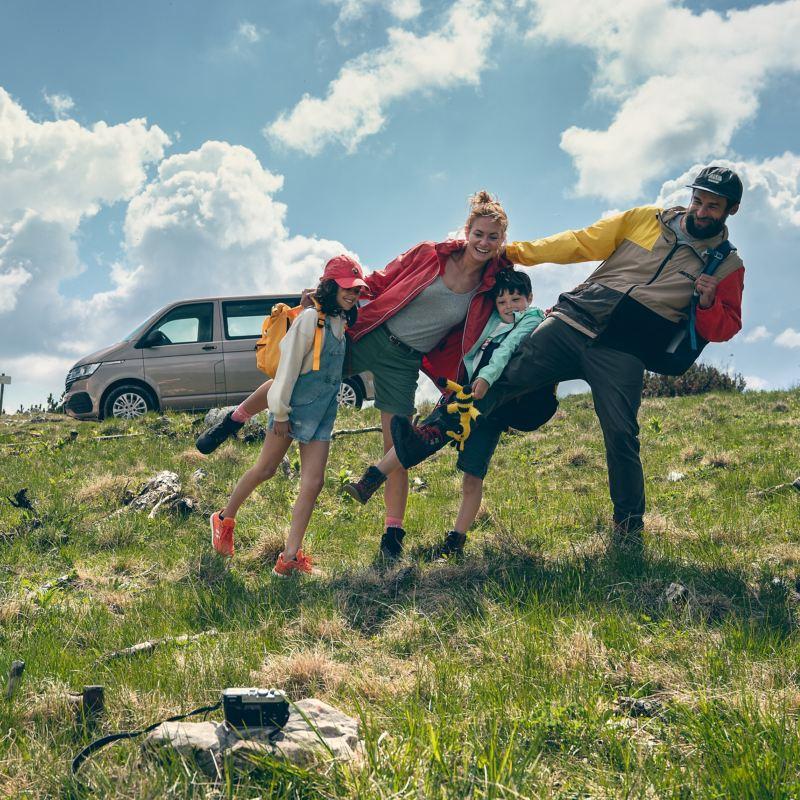 Eine Familie steht zusammen auf einem Berg. Im Hintergrund der Multivan 6.1 Family.
