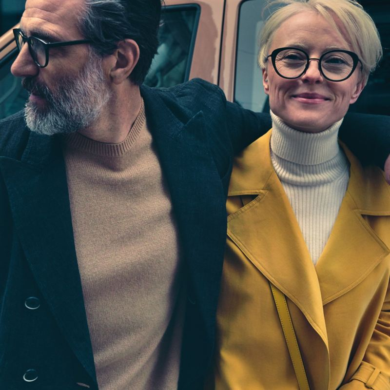 Un homme et une femme se tiennent par le bras devant une Volkswagen.