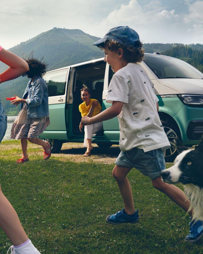 Der Multivan 6.1 Comfortline mit spielenden Kindern vor einem See.