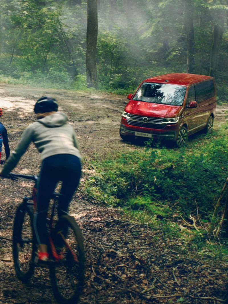 Trzy osoby jadą na rowerach w lesie. W tle czerwony Volkswagen Multivan 6.1.