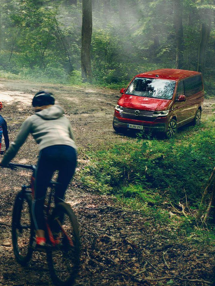 Persone in bici vicino a Volkswagen Multivan