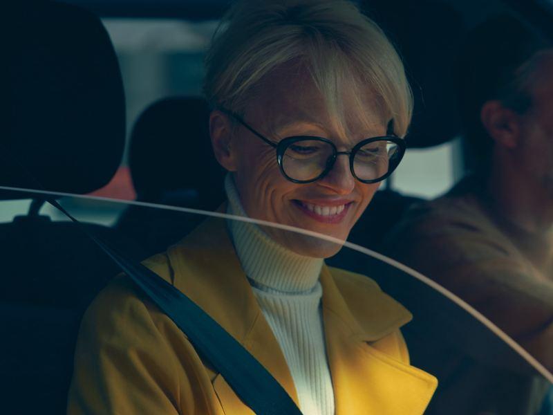 Eine Frau sitzt auf dem Beifahrersitz und blickt lachend nach unten.