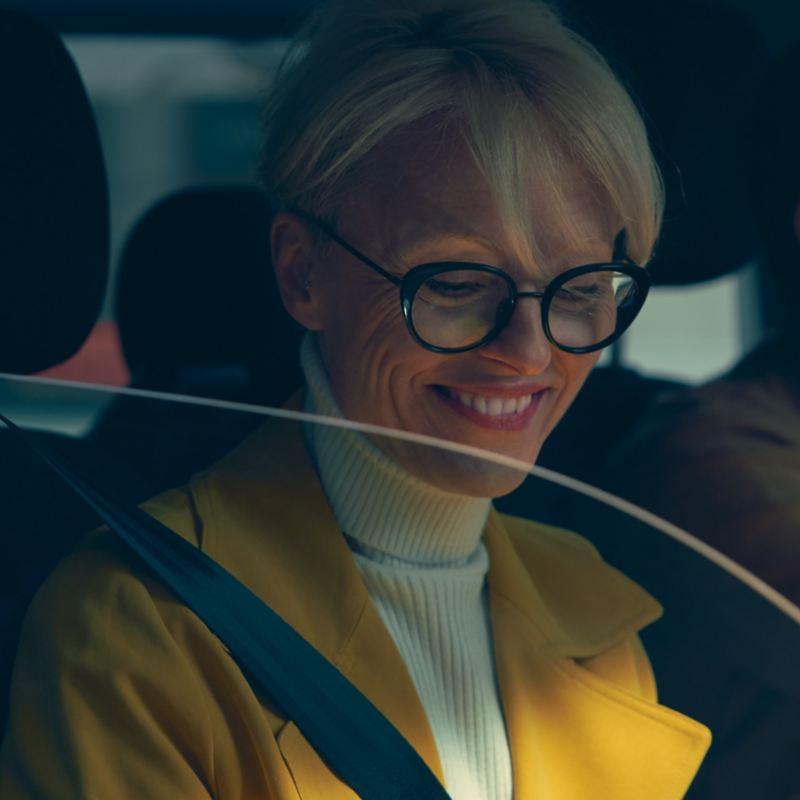 Una donna siede sul sedile del passeggero e guarda in basso sorridendo.