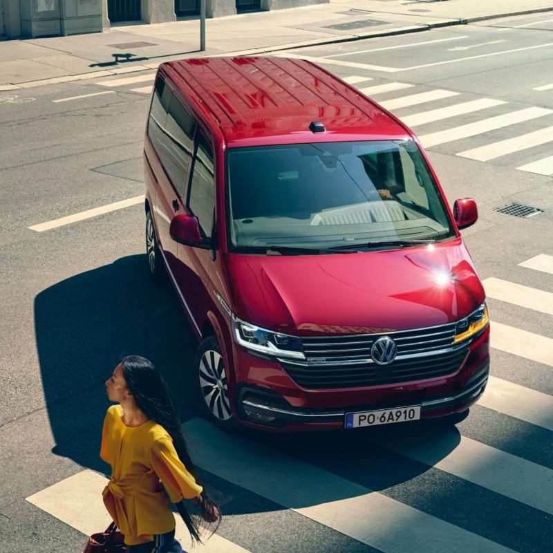 Czerwony Volkswagen Multivan 6.1. przejeżdża przez miasto.