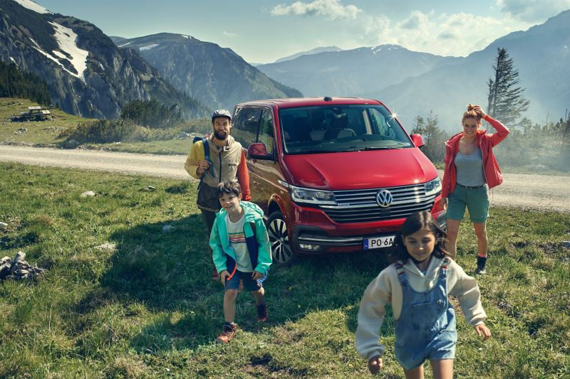 Rodzina obok czerwonego Volkswagen Multivan 6.1.