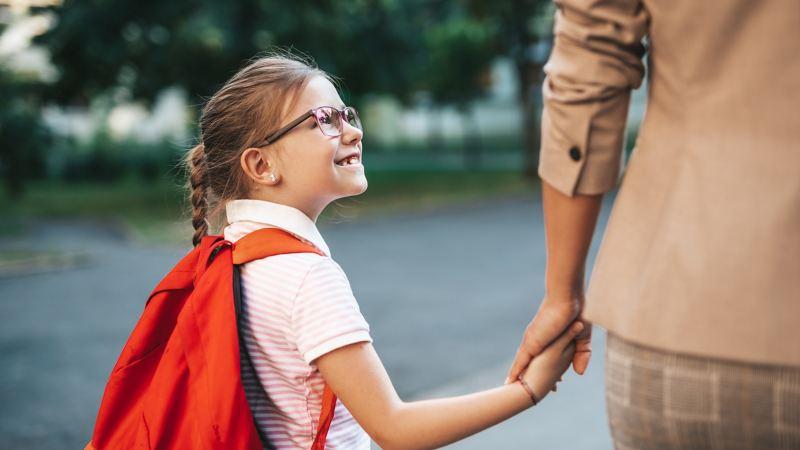 Mutter bringt ihre Tochter in die Schule.