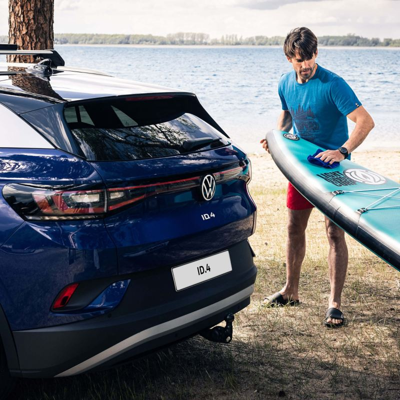 A man holding  surf board at the back of an VW ID.4