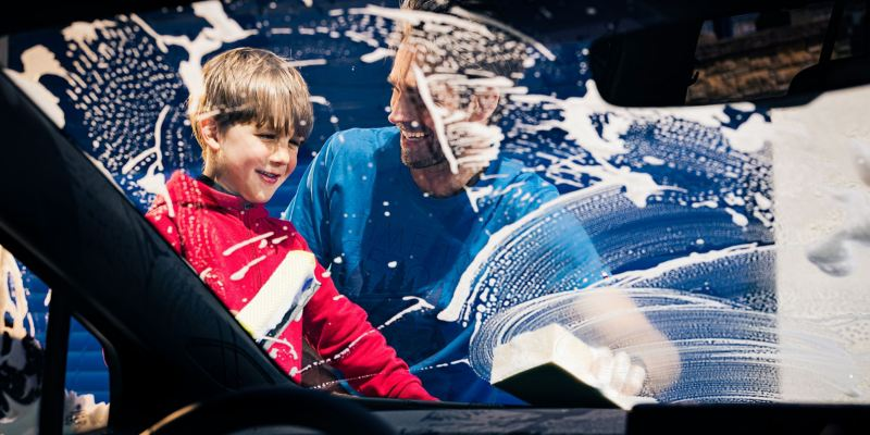 A man and his son clean the windshield of their Volkswagen with VW care products