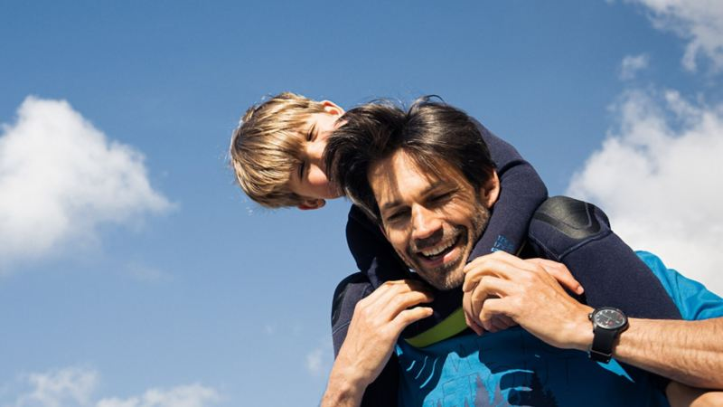 A boy sitting on his father's shoulders