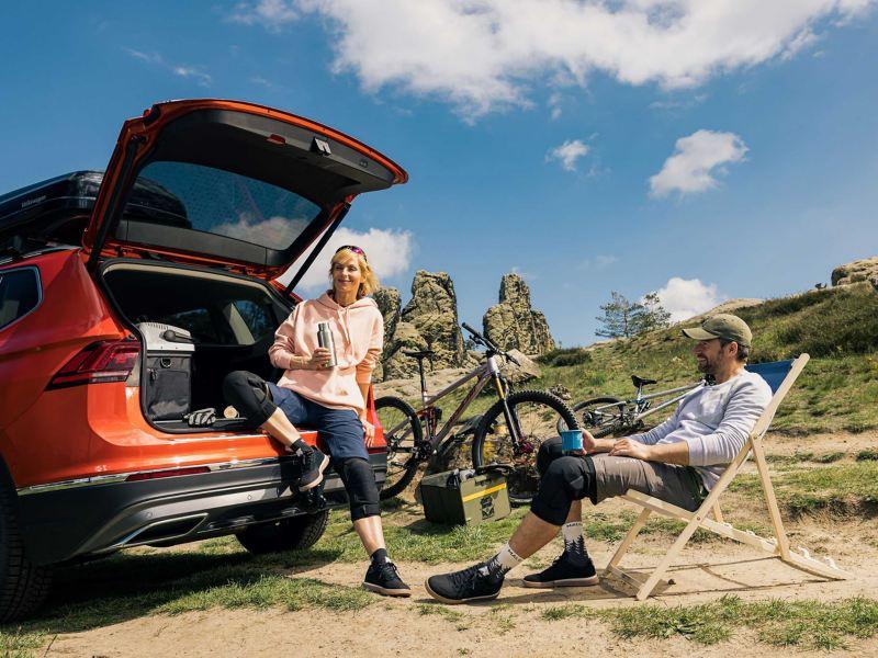 A woman and a man take a break next to their VW car