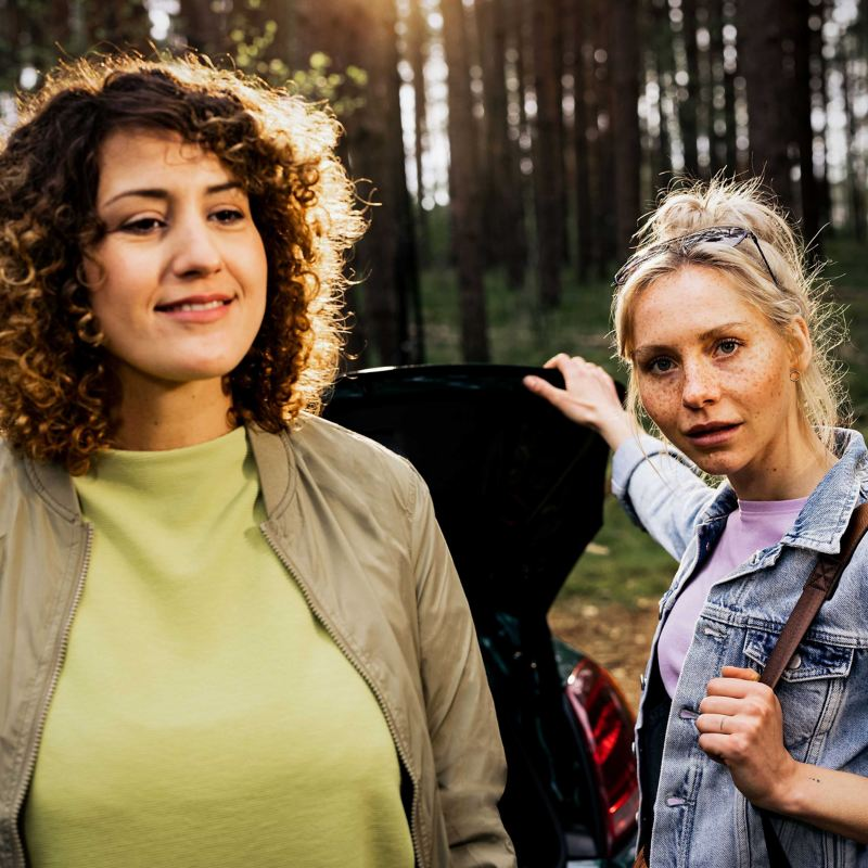 Two women at the luggage compartment of their VW – an outdoor trip with the Volkswagen