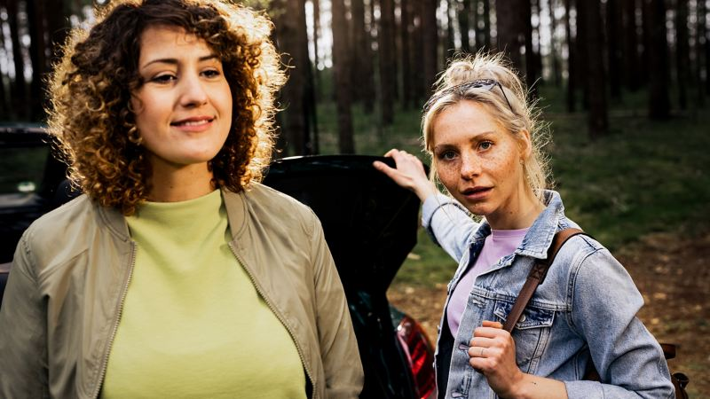 Two women at the luggage compartment of their VW – trip with the Volkswagen